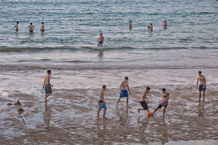 It is Sunday, I am going to take a little break from Asia and take you to the beautiful beach of La Concha in San Sebastian Spain where a group takes advantage of the low tide for a game. SPAIN San Sebastian Travel Documentary Storytelling Group Of People Water Beach Sea Real People Men Land People Leisure Activity