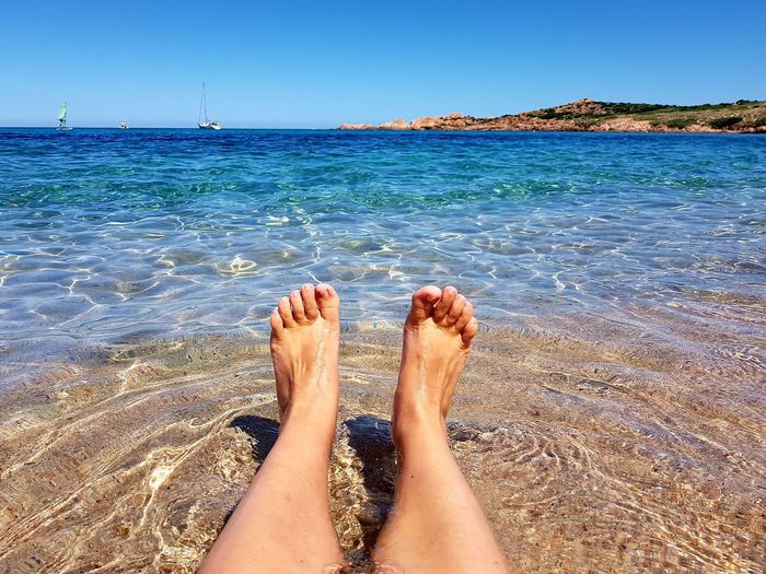 Low section of woman relaxing in sea against clear sky