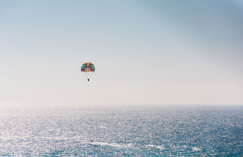 Distant view of person parasailing over sea against clear sky