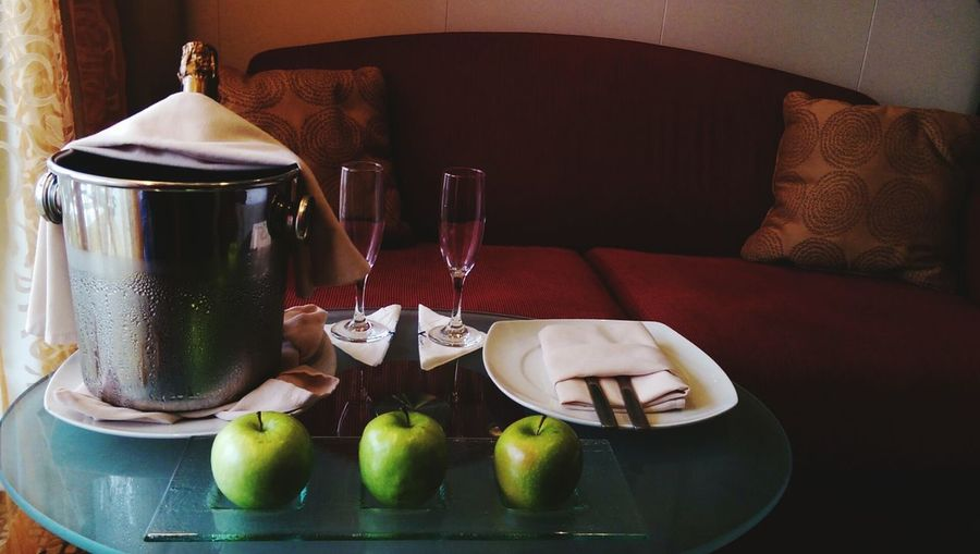 Champagne bottle in ice bucket by granny smith apples on table in cruise ship