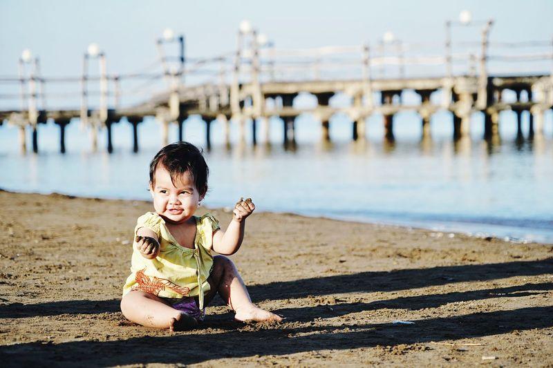 Full length of cute baby girl sitting at beach against bridge