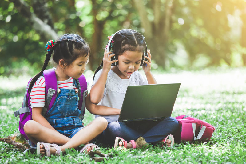 Schoolgirls Using Laptop While Sitting In Park
