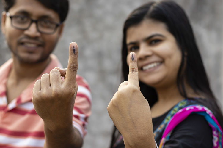 Indian man and woman showing ink-marked fingers with smiling faces after casting vote