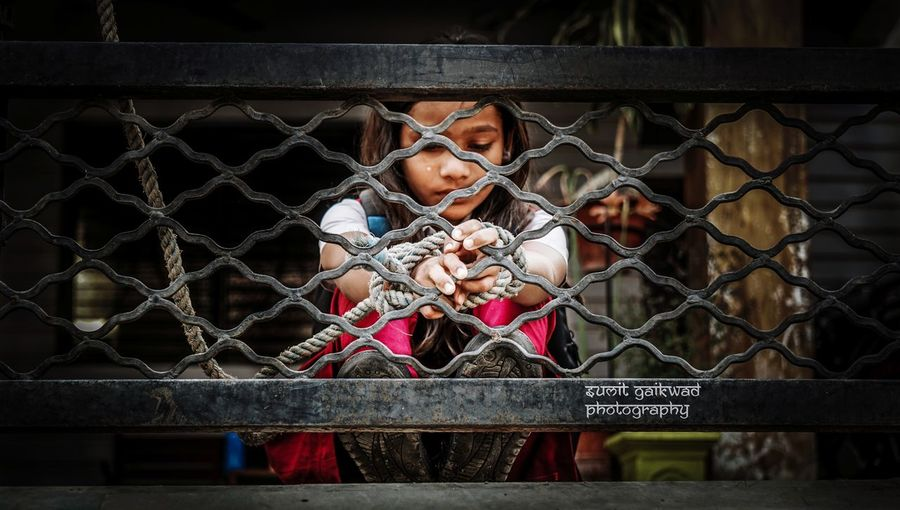 Girl Tied With Rope On Metal Railing
