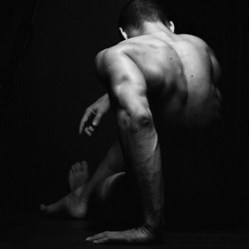 Rear View Of Shirtless Man Sitting Against Black Background