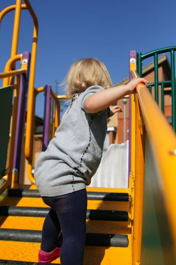 Rear view of girl playing in playground