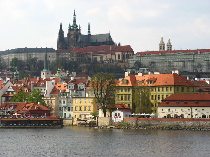 St vitus cathedral by vltava river against sky