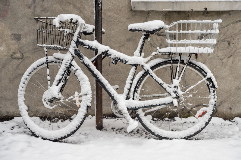 Close-Up Of Snow Covered Bicycle Parked Against Wall