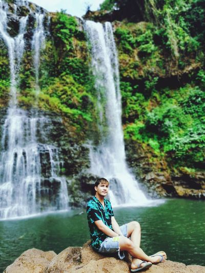 Man sitting on rock against waterfall in forest