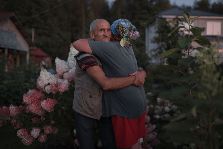 Senior couple embracing amidst plants