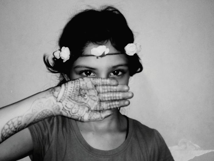 Portrait of girl wearing tiara showing henna tattoo against wall at home