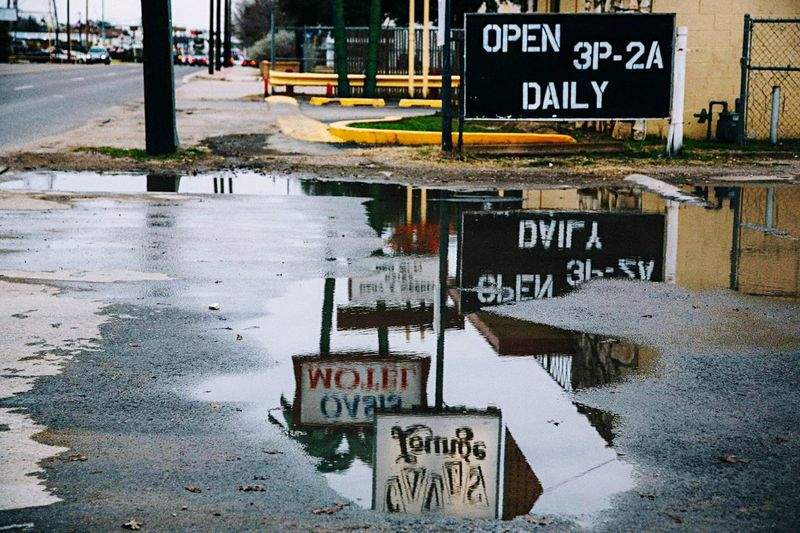 Reflecting signs Old Downtown Puddle Street Urban Street Photography Communication Text Sign Information Road Water City Reflection No People Outdoors Guidance Architecture Wet