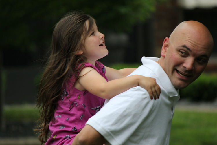 Playful Father Carrying Daughter On Back