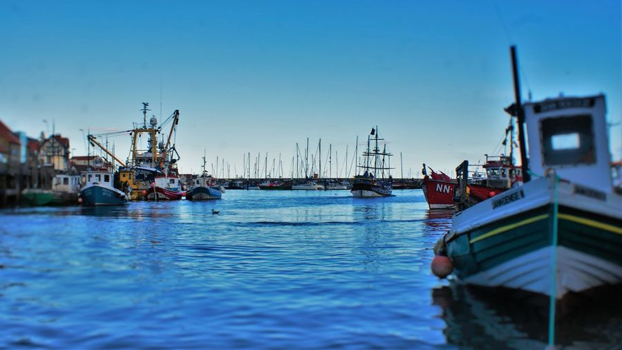 Boats moored in sea against clear sky