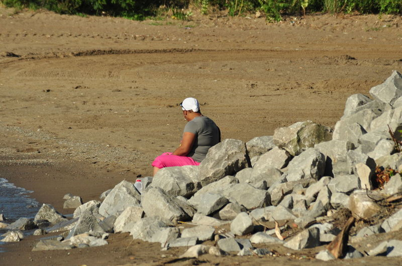 Side View Of Woman Sitting On Rocks At Beach