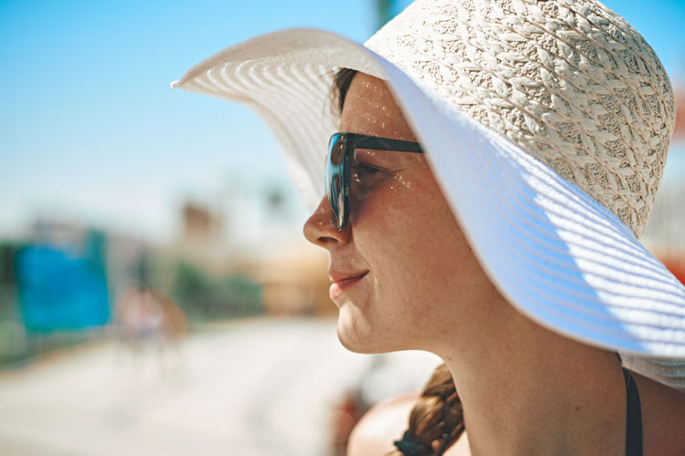 Close-up of woman wearing hat looking away outdoors
