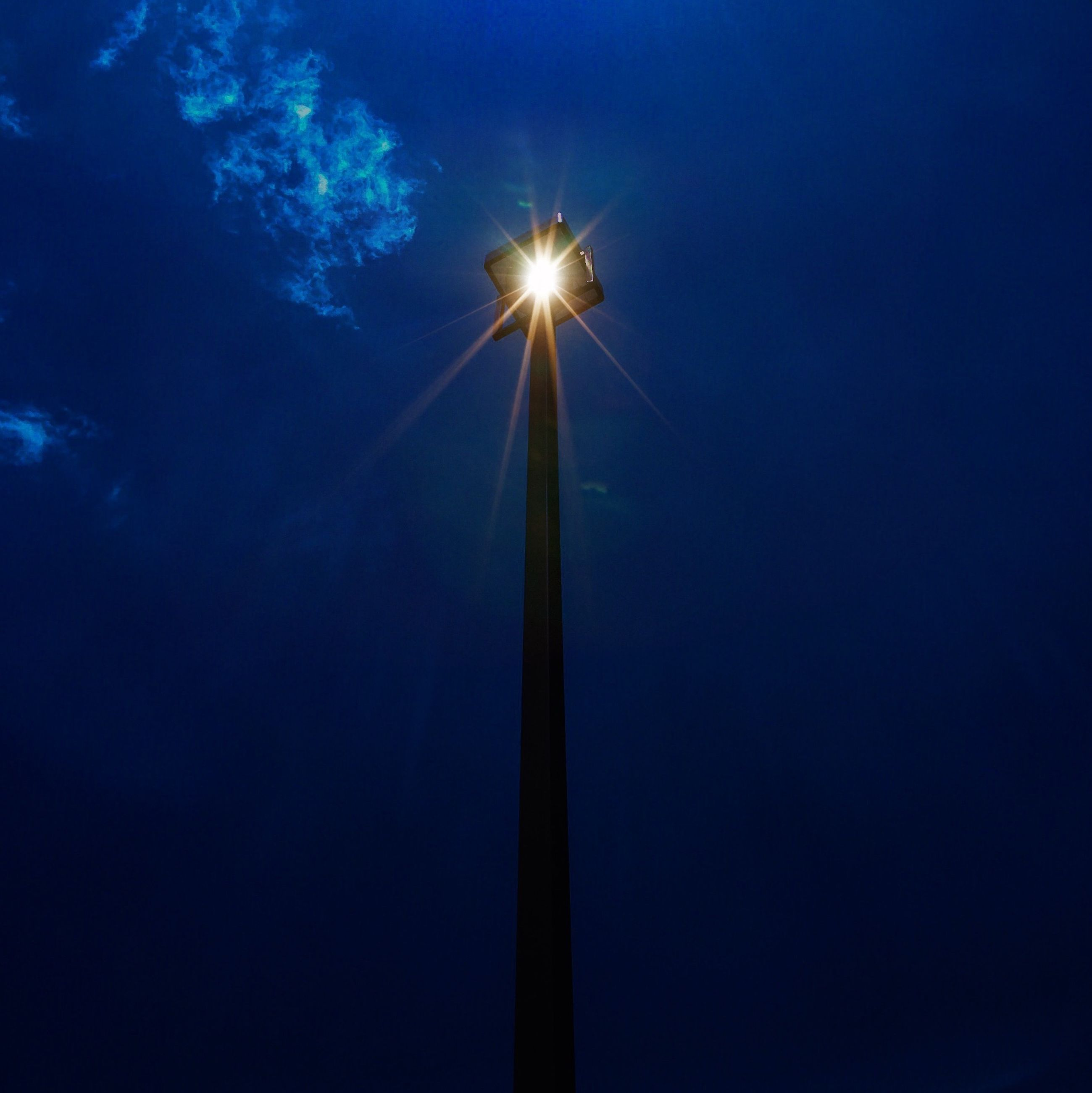 low angle view, blue, night, clear sky, silhouette, sun, sky, copy space, street light, lens flare, glowing, lighting equipment, sunlight, nature, electricity, sunbeam, moon, tranquility, outdoors, illuminated