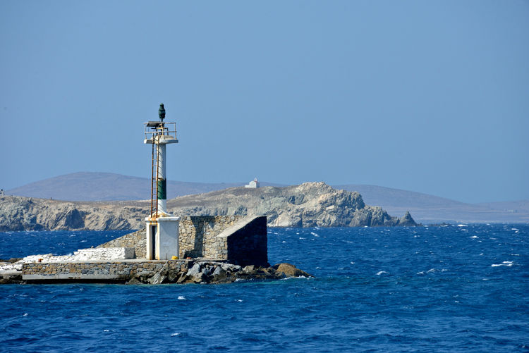 panoramic seaview of a lighthouse equipment on a pier in Mykonos Water Sky Sea Blue Built Structure Tower Clear Sky Nature Mountain Beauty In Nature Scenics - Nature No People Day Waterfront Building Exterior Building Guidance Copy Space Lighthouse Outdoors Lighting Equipment Maritime Nautical Nautical Equipment Pier Seascape Mykonos,Greece Navigation Light