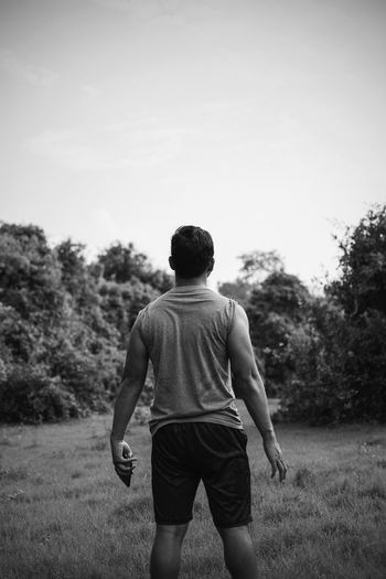 Rear view of man on field against sky