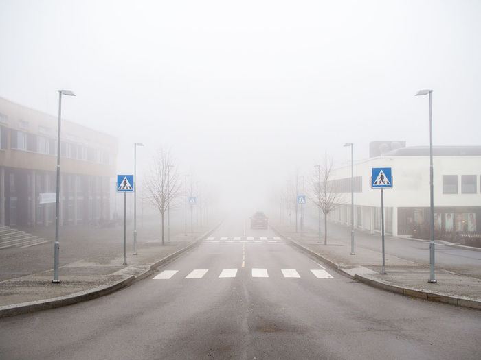 Road amidst buildings in foggy weather