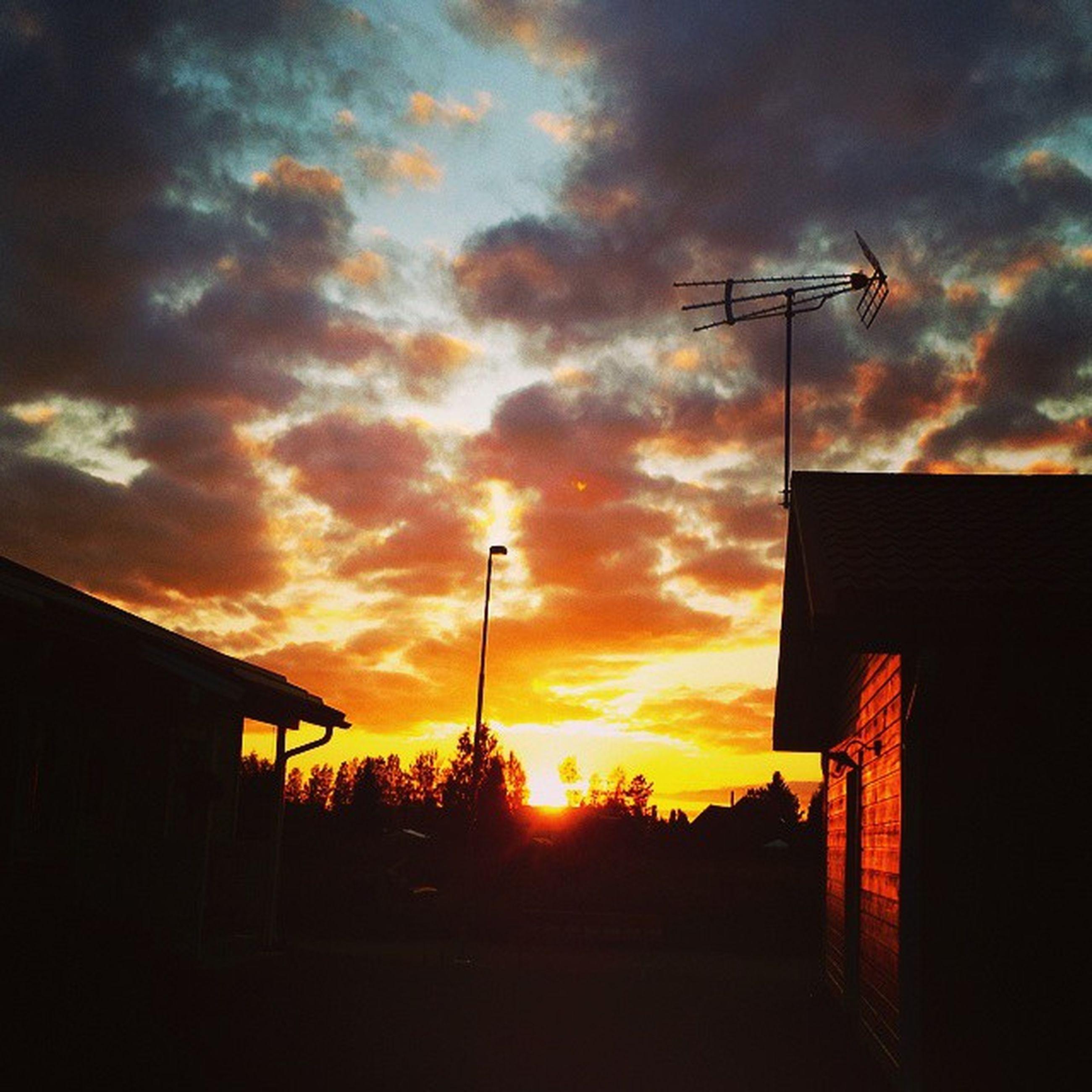 sunset, building exterior, architecture, built structure, sky, silhouette, orange color, cloud - sky, house, residential structure, residential building, street light, cloud, building, cloudy, city, sun, low angle view, outdoors, sunlight