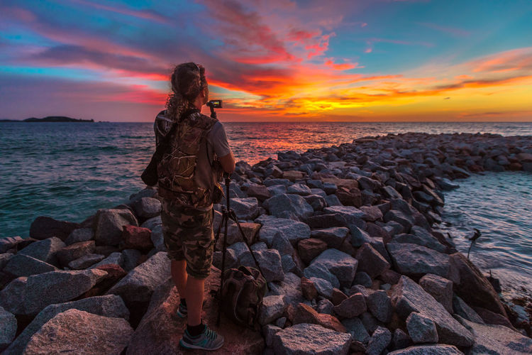 Man photographing while standing on rocks at beach against sky during sunset