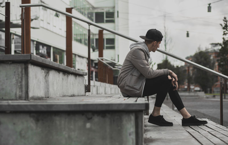 Young Man Sitting On Stepping In An Urban Space.