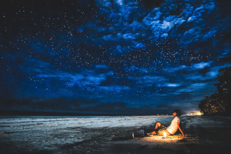 People sitting on beach against star field at night