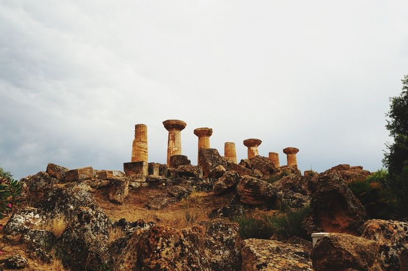 Low angle view of old ruins on hill against sky