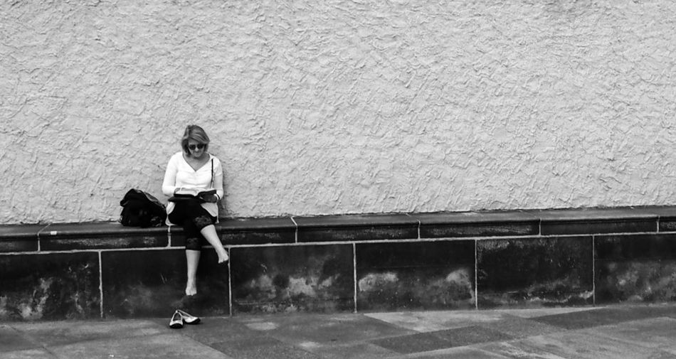 Full length of woman reading book while sitting on retaining wall against wall