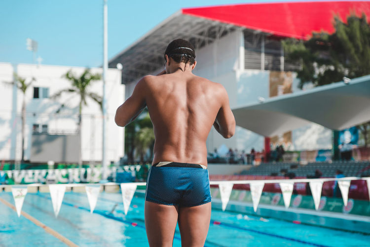 Rear view of swimmer standing by swimming pool