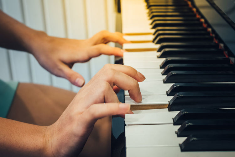 Cropped Hands Of Woman Playing Piano At Home