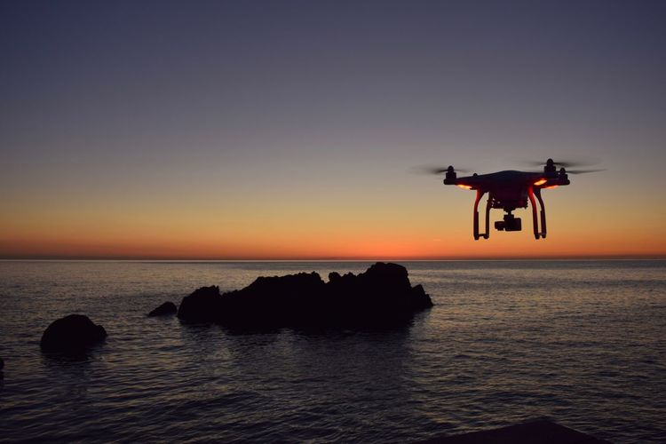 Drone flying over sea during sunset