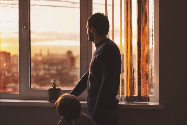 Rear view of boy by father looking towards window at home