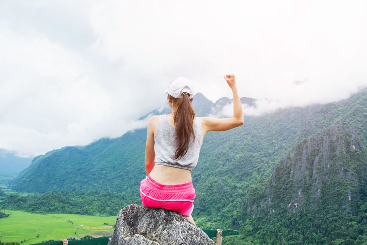 Adult Arms Raised Beauty In Nature Day Landscape Leisure Activity Lifestyles Mountain Nature One Person Outdoors People Real People Rear View Scenics Sky Standing Young Adult Young Women
