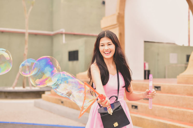 Architecture Beautiful Woman Beauty Bubble Built Structure Casual Clothing Front View Hair Hairstyle Happiness Leisure Activity Lifestyles One Person Outdoors Real People Smiling Standing Three Quarter Length Women Young Adult Young Women