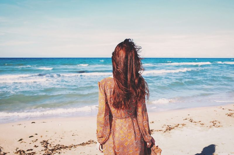 Rear view of woman overlooking calm blue sea