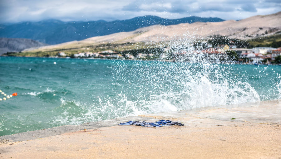 Wet towel laying on a pier with waves splashing and hitting the pier in a coastal storm. Beach Croatia Day Motion Mountain Nature No People Outdoors Pag Sea Sky Water Wave Wind