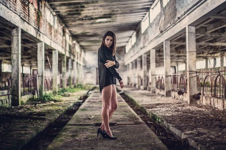 Portrait of beautiful woman standing on concrete in abandoned factory