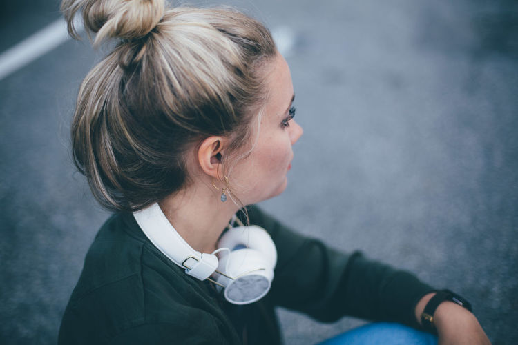Side view of young woman with headphones sitting on road