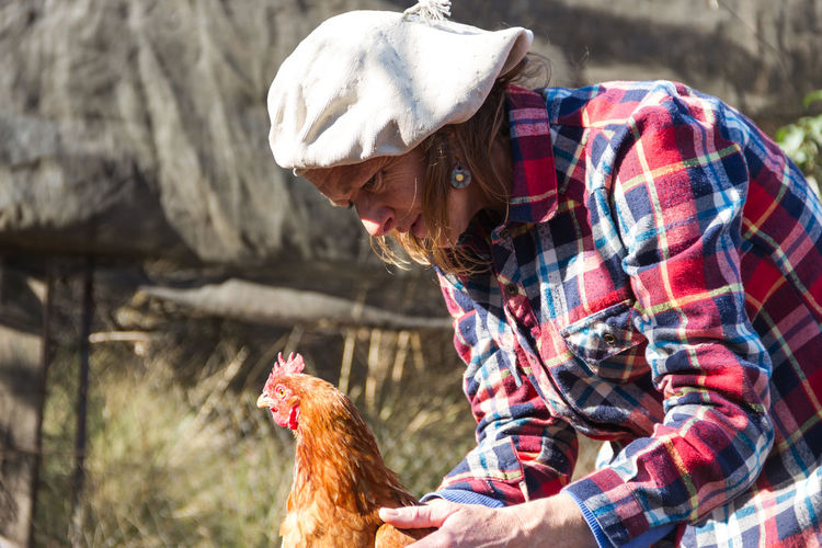 Mature woman with hen at farm
