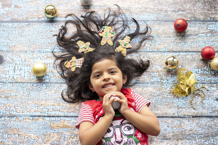 Portrait of smiling girl with christmas ornament on floorboard