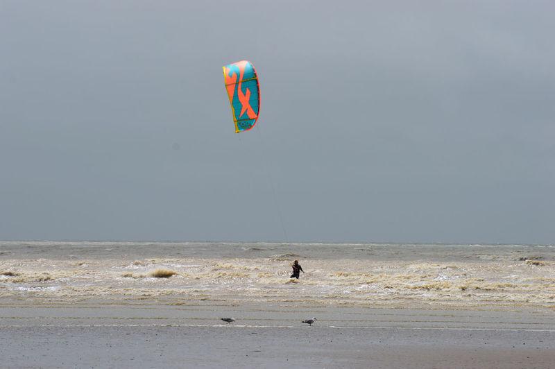 People on beach by sea against sky