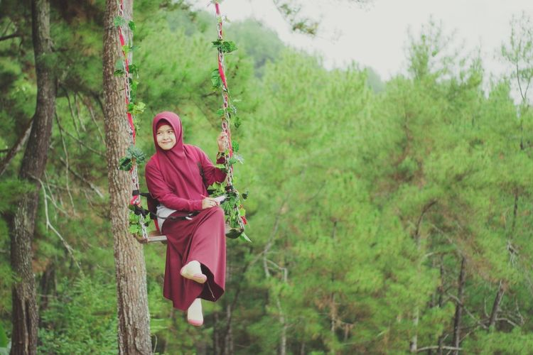 Full length of young woman on swing against trees at forest