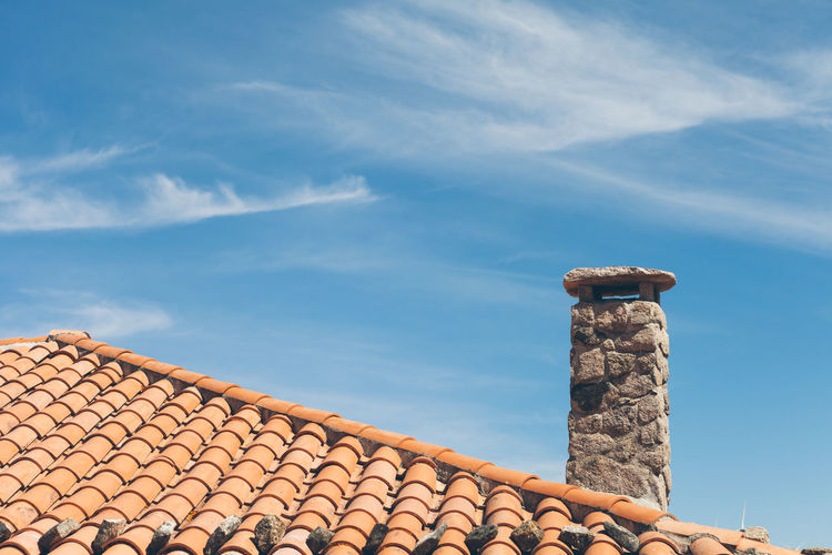 Low angle view of chimney on roof against sky