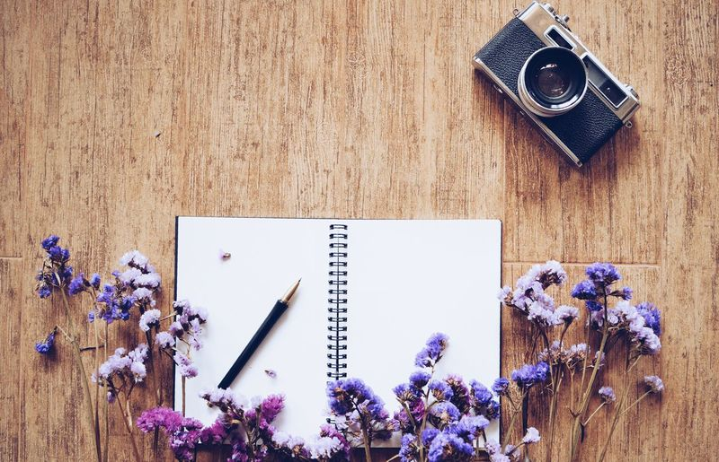 top view of blank space notebook paper and pen on wooden texture background #copy Space #flower  #notebook #paperbond #PAPERROLLS #spring #texture #vintage Camera