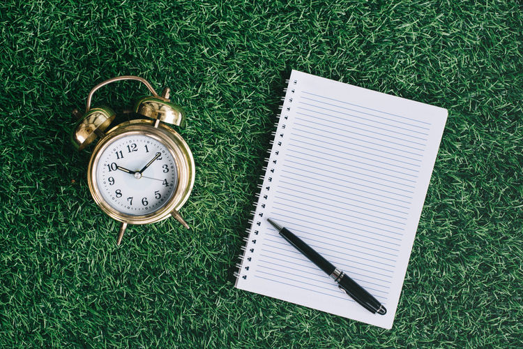 Blank notebook copy space with alarm clock
