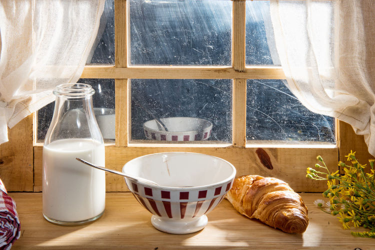Close up of milk and croissant with bowl against window