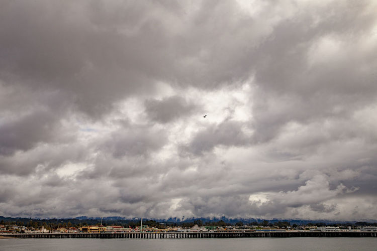 Scenic view of bridge over river against cloudy sky