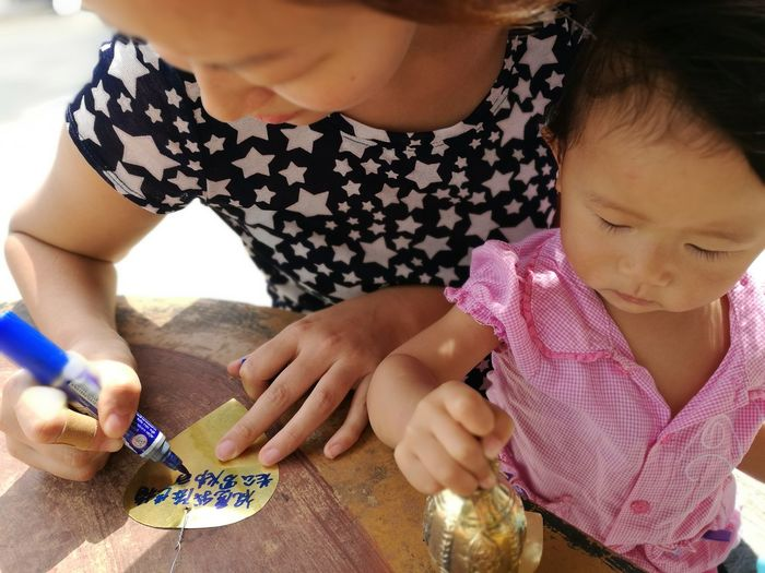 High angle view of woman with little girl writing prayer message